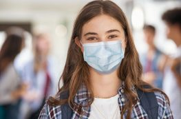 Portrait of girl wearing a face mask standing in college campus